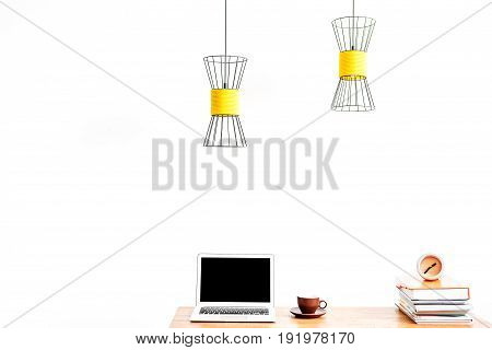 Close up of laptop with coffee cup on saucer and pile of books with alarm clock on top on table surface. Lusters hanging over place of work. Copy space in left side and isolated