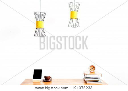Close up of tablet with coffee cup on one side and pile of books and alarm clock on other side of table surface. Chandeliers hanging over workplace. Isolated