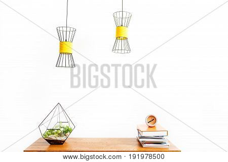 Close up of clock on top of pile of books and vase with domestic plants on table surface. Chandeliers hanging over workplace. Education concept. Isolated