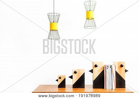 Close up of decorative birds of different sizes with pile of copybooks between them on table. Ceiling lamps hanging over workplace. Isolated