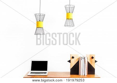 Close up of laptop and decorative wooden birds with pile of books between them on table. Ceiling lamps hanging over workplace. Isolated