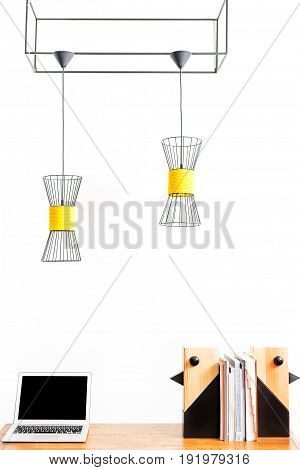 Close up of notebook and two wooden decorative birds with pile of books between them on table. Chandeliers hanging over workplace from huge metallic parallelogram. Isolated