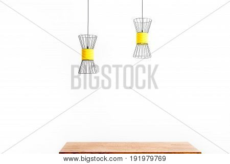 Close up of metallic chandeliers hanging over wooden table surface. Isolated