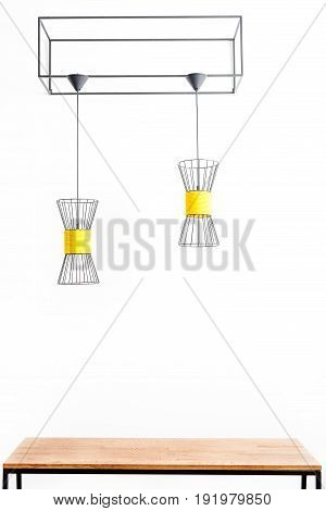 Close up of chandeliers hanging from metallic geometric construction over table. Isolated
