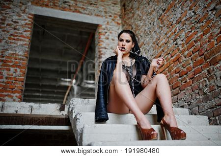 Brunette Plus Size Sexy Woman, Wear At Black One Piece And Leather Jacket,with Chain At Abadoned Pla