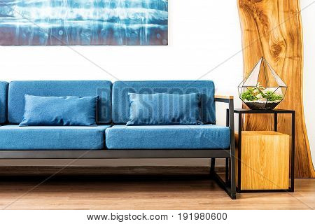 Close up of sofa nearby of cubic stand with domestic plant vase on top and wooden wardrobe. Huge picture hanging above couch