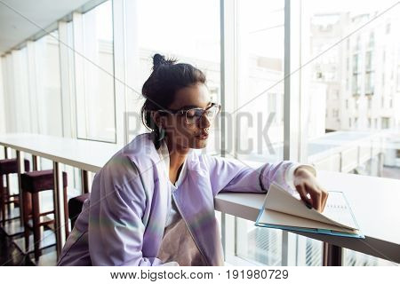 young cute hipster girl student sitting in cafe with notebook reading, wearing glasses, lifestyle happy smiling people concept close up