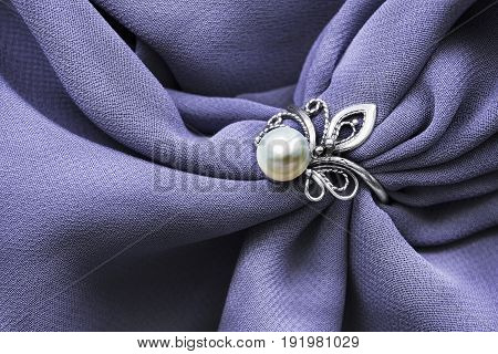 Vintage silver pearl ring on draped violet silk closeup