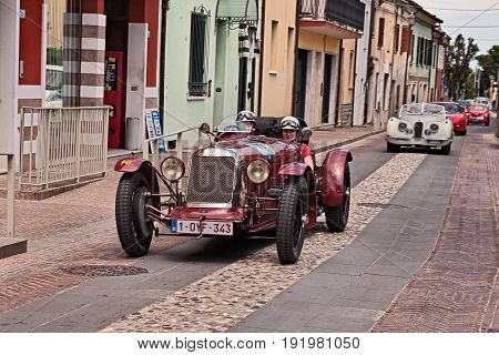 GATTEO, FC, ITALY - MAY 19: driver and co-driver on an old competition car Maserati tipo 26M 8C 2500 (1930) in historical classic car race Mille Miglia, on May 19, 2017 in Gatteo, FC, Italy