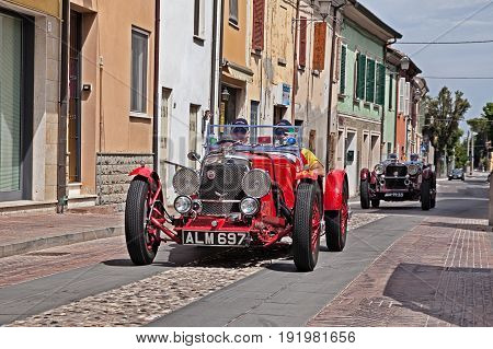 GATTEO, FC, ITALY - MAY 19: driver and co-driver on an old racing car Aston Martin Le Mans (1933) during the historical classic car race Mille Miglia, on May 19, 2017 in Gatteo, FC, Italy