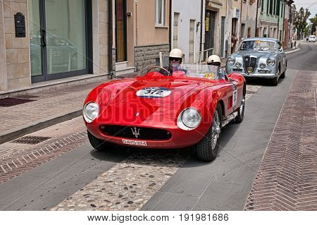 GATTEO, FC, ITALY - MAY 19: driver and co-driver on a vintage racing car Maserati 150 S (1955) during the historical classic car race Mille Miglia, on May 19, 2017 in Gatteo, FC, Italy
