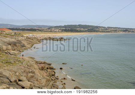 LA TOJA, SPAIN - AUGUST 8, 2016: Crowed beach along the coast of the Island of La Toja in the province of Pontevedra Galicia Spain.