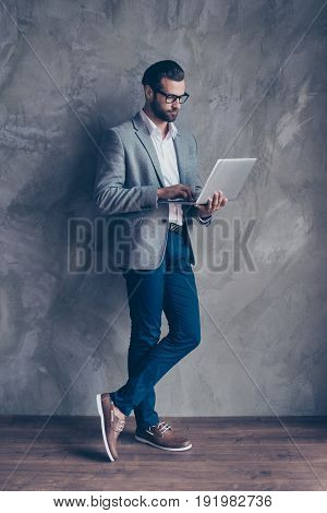 Full Length Of Serious Confident Concentrated Bearded Man In Formal Wear Typing On His Laptop, He Is