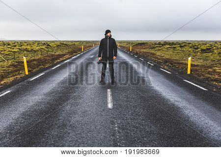 Photographer portrait standing on the road in Iceland. Young man wearing warm clothes standing in the middle of the Ring Road in Iceland looking away from camera. Travel and wanderlust concepts