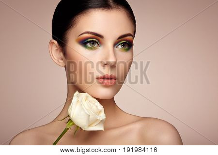 Portrait of beautiful young woman with rainbow make-up. Girl summer. Long eyelashes vivid colorful eyeshadows. White rose. Multicolored