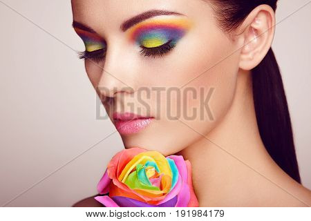 Portrait of beautiful young woman with rainbow rose. Bright colors. Long eyelashes vivid colorful eyeshadows. Rainbow make up. Multicolored flowers