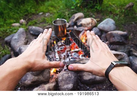 Men's hands are warming around the campfire in the forest