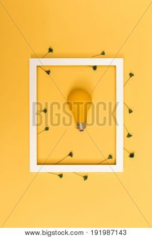 Yellow painted light bulb with picture frame on a vibrant background