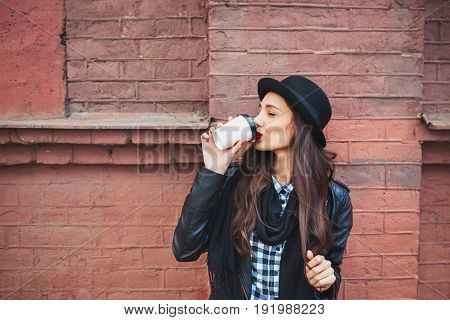young beautiful brunette drinking coffee walking around the city.leather jacketurban backpack bright red lips and hat