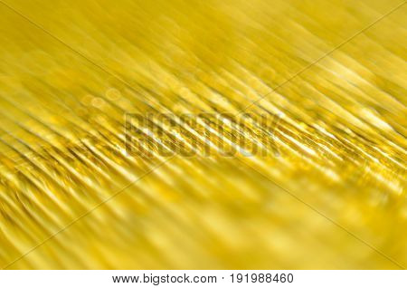 Gold Texture of Embossed Paper. Gold Paper Texture Background. Macro. Shallow depth of field. Abstract background with deep grooves in the texture of corrugated paper