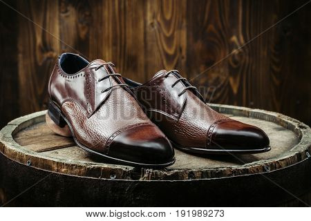 Stylish men's shoes on a wooden table on a dark wooden background