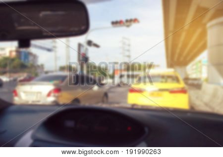 abstract blurred image of view from inside car vintage tone color and sunlight effect traffic jam on street in the city transportation and travel concept