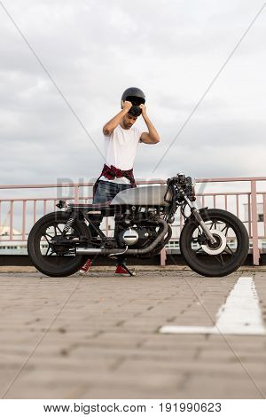 Handsome rider guy with beard and mustache posing while put on black moto helmet near classic style biker cafe racer motorcycle. Bike custom made in vintage garage. Brutal fun urban lifestyle.