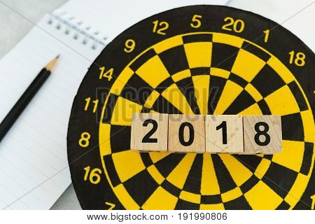 Next year planning target concept with wooden blocks number 2018 on dart board and pencil.