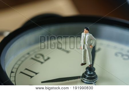 business or time countdown concept as miniature businessman figure standing on alarm clock.