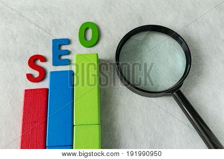 SEO Search engine optimization concept as colorful wooden block as analysis chart with alphabet abbreviation SEO and magnification glass on white texture paper.
