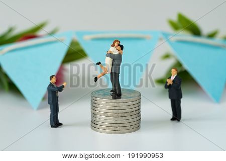 Miniature people with couple standing on top stack of coins and other clapping as success love life concept.