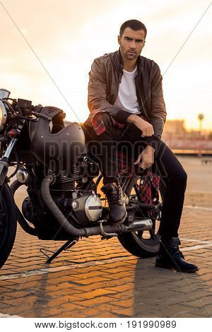 Handsome rider guy with beard and mustache in black leather biker jacket boot and jeans sit on classic style cafe racer motorcycle. Bike custom made in vintage garage. Brutal fun urban lifestyle.