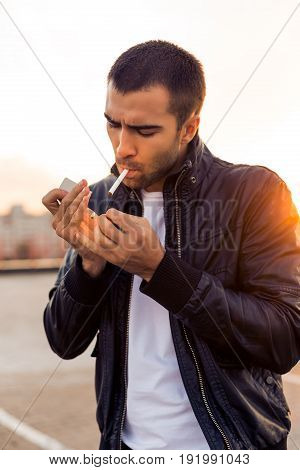 Close up portrait of a handsome rider guy with beard and mustache in black biker jacket white t-shirt and fashion sunglasses light up cigaret on rooftop at sunset. Brutal fun urban lifestyle.