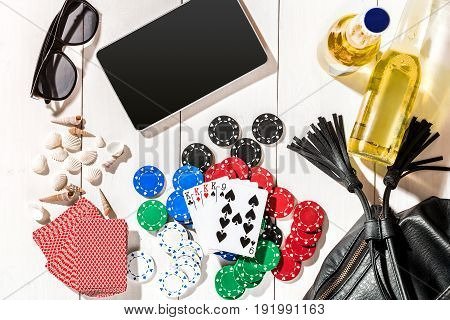 Card deck surrounded by poker chips and scattered seashells, glasses, a tablet and two bottles of beer, on white wooden background with copy space