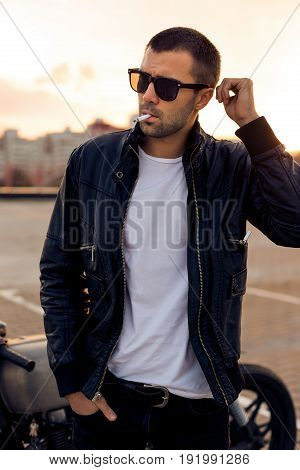 Handsome rider man with beard and mustache in black biker jacket white t-shirt and sunglasses smoking cigaret near classic style cafe racer motorbike on rooftop at sunset. Brutal fun urban lifestyle.