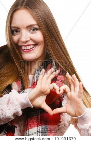 Portrait of long hair girl in bright sweater and warm woolen big scarf making heart shape by hands. Winter fashion.
