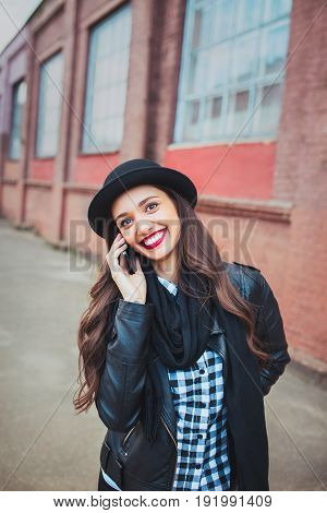 Young stylish woman talking on the phone and smiling in a city street