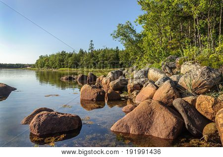 Large stones on the shore of the White Sea Bolshoy Solovetsky Island Russia. Sunny summer evening.