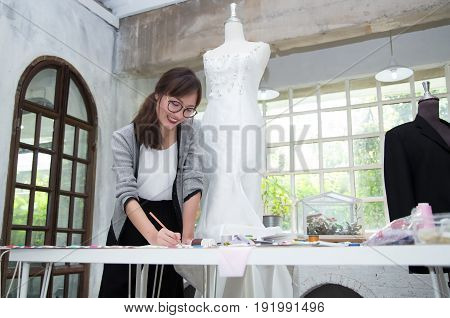 Young female fashion designer are working on drafting a new clothes on the table in studio.