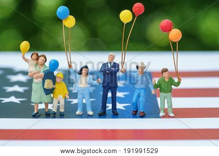 miniature figure happy american family holding balloon with United State national flag in green bokeh background as celebrating the Independence day.