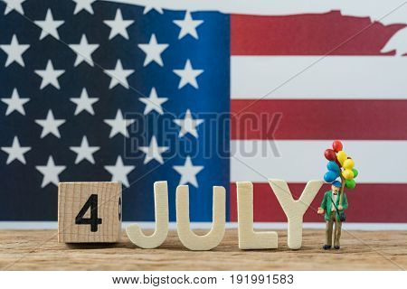 Independence day USA miniature people old man holding balloon with wooden cube number 4 and alphabets JULY and United State national flag in the background.
