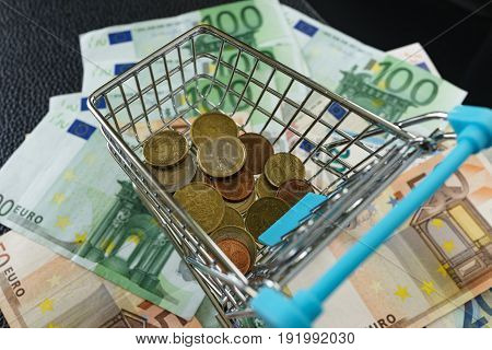 Selective focus on Euro coins in mini shopping cart on pile of euro banknote on background as shopping concept.