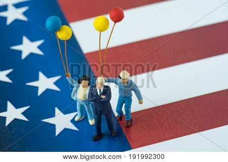 Independence day celebration with miniature happy american family holding balloons standing on United State national flag background.