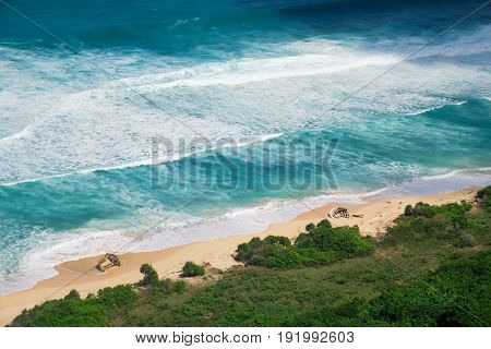Amazing outdoor nature landscape photography with paradise view above the sea shoreline. Idyllic aerial view of an empty tropical beach and vivid blue sea white foam waves in Bali, Indonesia.