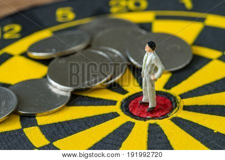 financial business concept as miniature businessman standing at the center of dartboard red dot with coins around.