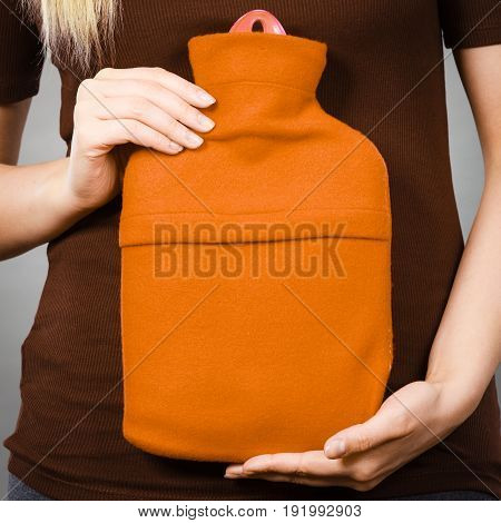 Woman holding warm orange hot water bottle. Fever flu treatment objects concept.