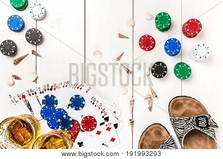 Card deck surrounded by poker chips and scattered seashells, glasses, flip flops, two glasses of whiskey with ice on white wooden background with copy space