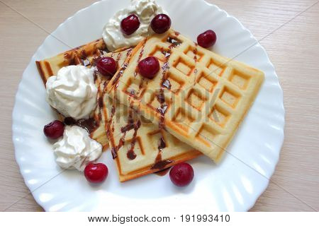 belgian waffles with cream chocolate sauce and cherries on a white plate