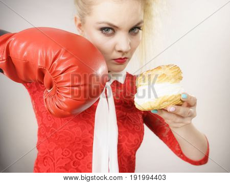 Dieting weight loss concept. Funny blonde woman holding yummy choux puff cake with whipped cream and boxing glove fighting off bad food. On grey