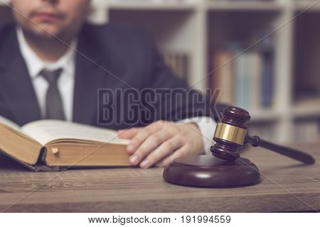 Detail of a judge sitting at his desk studying new laws and legislation. Focus on the judge gavel